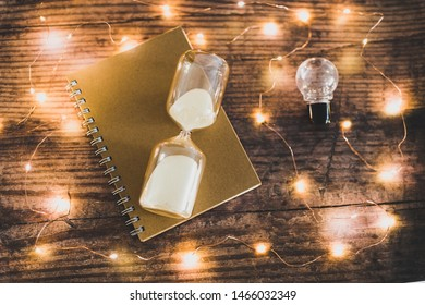 time to accomplish your goals conceptual image with hourglass, lightbulb and to do list notebook surrounded by fairy lights bokeh on wooden office desk