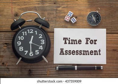 Time For Assessment written on paper with wooden background desk,clock,dice,compass and pen.Top view conceptual