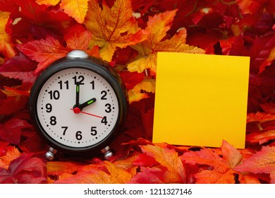 It is time for Autumn , Some fall leaves and black and white alarm clock and yellow sticky note with copy-space