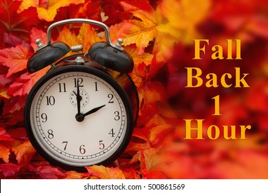 It is time for Autumn, Some fall leaves and black and white alarm clock with copy-space