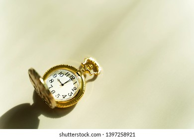 Time background concept. Golden pocket watch on table with sunlight and free copy space for text.