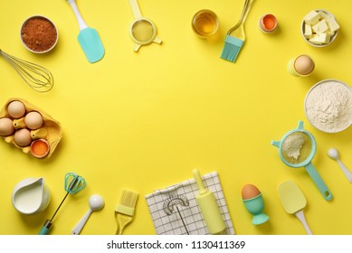 Time to bake. Baking ingredients - butter, sugar, flour, eggs, oil, spoon, rolling pin, brush, whisk, towel over yellow background. Bakery food frame, cooking concept. Top view, copy space. Flat lay.