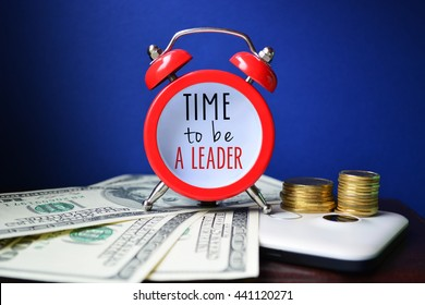 Time to be a leader. Sign on red clocks with cash and coins on background