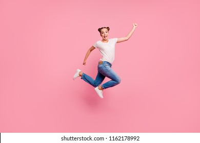 Time to be yourself! Full legh, body, size portrait of crazy and funny girl who jumps on the trampoline isolated on shine pink background