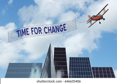 Time for Change banner pulled by plane over downtown office buildings