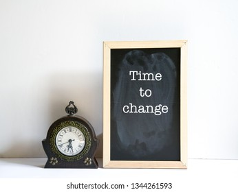 Time to change concept - message on board with an antique clock by the side
