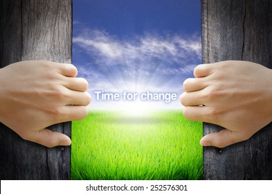 Time to Change motivational quotes. Hand opening an old wooden door and found a texts floating over green field and bright blue Sky Sunrise.