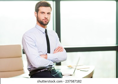 Time for coffee break. Handsome young man in shirt and tie holding coffee cup and smiling while leaning at the desk