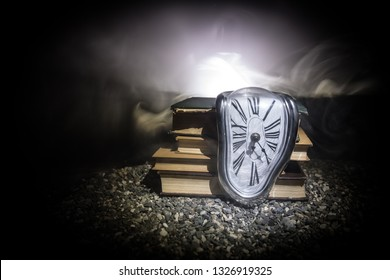 Time Concept. Distorted soft melting clock on a old books on dark toned foggy background. Selective focus