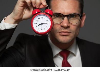 Time concept - handsome businessman in formal suit holding red clock