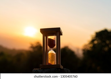 Time Concept Hourglass with sunrise in the morning at mountain.