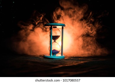 Time concept. Silhouette of Hourglass clock and smoke on dark background with hot yellow orange red blue cold back lighting, or symbols of time with copy space
