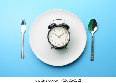 time consuming diet and health care concept. top view of the white plate with alarm clock, fork and spoon on blue dine table. flat lay. free copy space for your text
