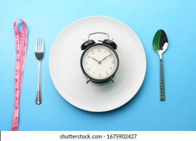 time consuming diet and health care concept. top view of the white plate with alarm clock, measurement tape, fork and spoon on blue dine table. flat lay. free copy space for your text