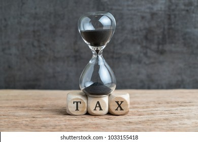 Time countdown for tax deadline concept, hourglass or sandglass on cube wooden block with alphabets TAX on wood table with dark black loft cement wall.