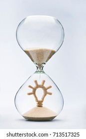 Time is creativity concept with falling sand taking the shape of a light bulb inside a hourglass