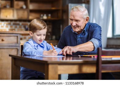 Time for creativity. Joyful senior man drawing with his grandson in the kitchen