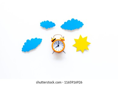 Time of day. Morning. Awakening and sunrise. Sun and clouds cutout near alarm clock on white background top view space for text