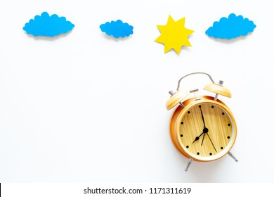 Time of day. Morning. Awakening and sunrise. Sun and clouds cutout near alarm clock on white background top view copy space