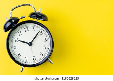 Time, deadline or reminder concept, vintage ringing black alarm clock with white face on yellow background in flat lay or top view, studio shot with copy space.