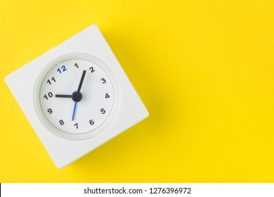 Time, deadline or reminder and schedule concept, minimal modern square alarm clock with white face on yellow background in flat lay or top view, studio shot with copy space.
