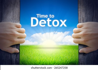 Time to Detox. Hands opening a wooden door then found a texts floating among new world as green grass field, Blue sky and the Sunrise.