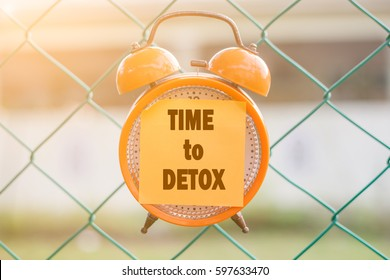 TIME TO DETOX word written on sticky note on orange analog clock hanging on the fence over blurry background