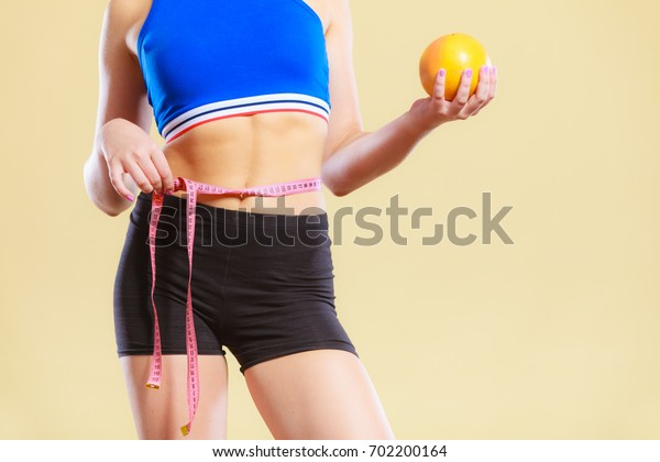 Time for diet slimming weight loss. Health care and healthy nutrition. Young fitness woman fit girl with measure tape and grapefruit