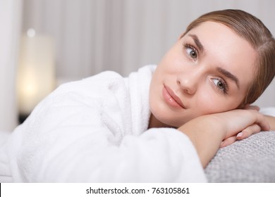 Time for dreams. Portrait of peaceful young woman lying on massage table with relaxation in white bathrobe