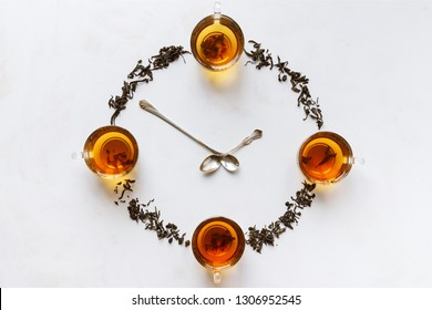 Time to drink tea. Cups of black tea and pouring tea form a clock.