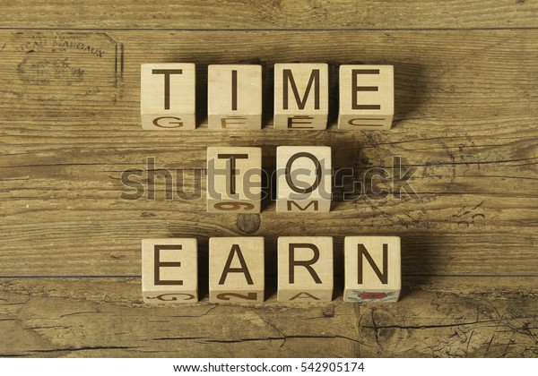 time to earn text on cubes on wooden background