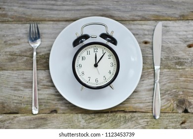 Time to eat with clock plate fork and knife on a table top view