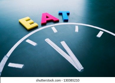 Time to eat concept, color word and clock on blackboard