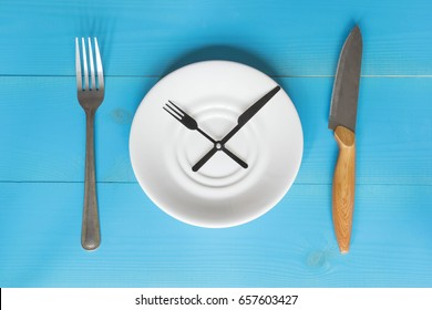 Time to eat concept, saucer as a clock, fork and knife on the blue wooden background.