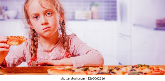 Time to eat! Cute little girl with pizza. Happy child having fun eating dinner. Food concept.