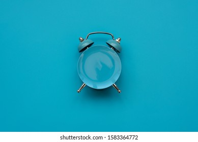 Time to eat. Empty plate as clock on blue background. Mock-up. Top view. Flat lay. Weight loss and diet concept