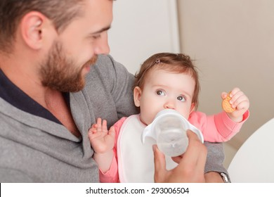 Time to eat. Selective focus of little child looking at father feeding it with baby bottle .