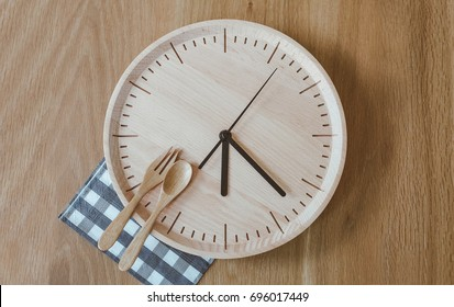 """Time to eat"",  Top view of spoon and fork on the wooden clock plate, wooden table background, with blank copy space"