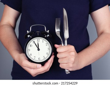 Time to eat. Woman's hands holding alarm clock with fork and knife. Five minutes before lunch.