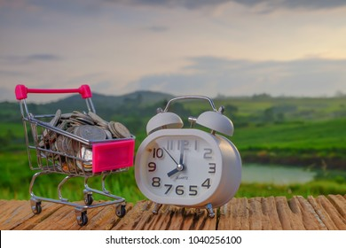 Time, e-commerce, saving and shopping concept. Mini shopping cart filled with coins with alarm clock on green background