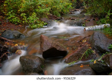 time elapsed photo of small creek, with rocks.