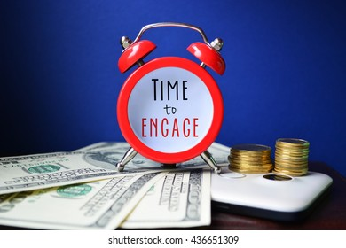 Time to engage. Sign on red clock with money and coins.