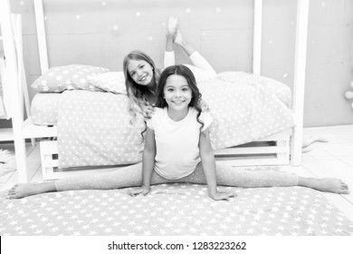 Time for evening stretching. Cute gymnast practice split with friend. Girl child sit split in bedroom. Friends gymnasts support each other. Sport regime lifestyle. Girl kid cute pajamas stretching.