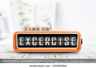 Time to excercise message on an alarm clock in a bright living room on a wooden table