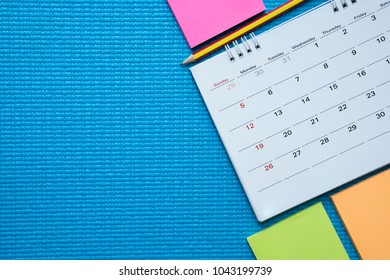 Time for exercising, calendar on the blue yoga mat background