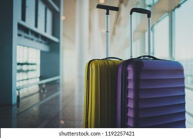 It's time to explore. Two travel suitcases in empty departure terminal, blank space for your text message or design, vacation concept, suitcases in airport waiting area hall with big light windows