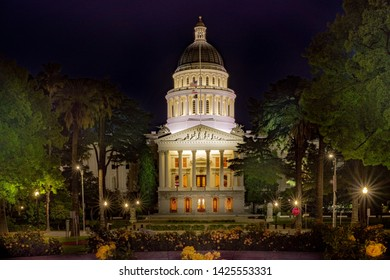 Time exposure of the front entrance to the California State Capital in Sacramento at night with yellow floral garden in foreground