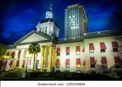 Time exposure of historic Florida State House with red and white striped awnings in Tallahassee illuminated at sunset with modern capitol skyrise in background and palm trees in front.