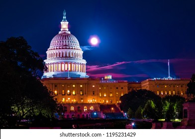 Time exposure of illuminated dome of the white United States capital building at night with full moon in background.