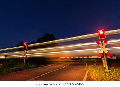 Time exposure, passenger train passes a barrier at night